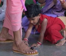 Little child touches a priest's feet